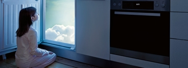 Photo composition with a child in front of a refrigerator, looking into clouds