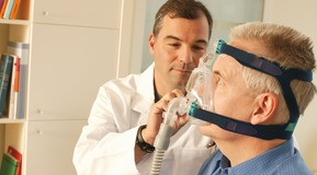 Pulmologist/doctor showing sleep apnea patient  CPAP device and sleep mask used for home sleep therapy.